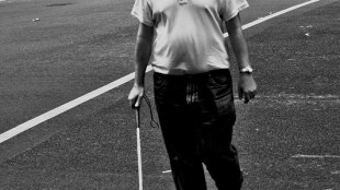 A blind man walking on the road with a white cane in his right hand