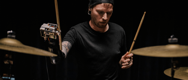 Jason Barnes playing drums wearing his AI powered robotic prosthetic arm