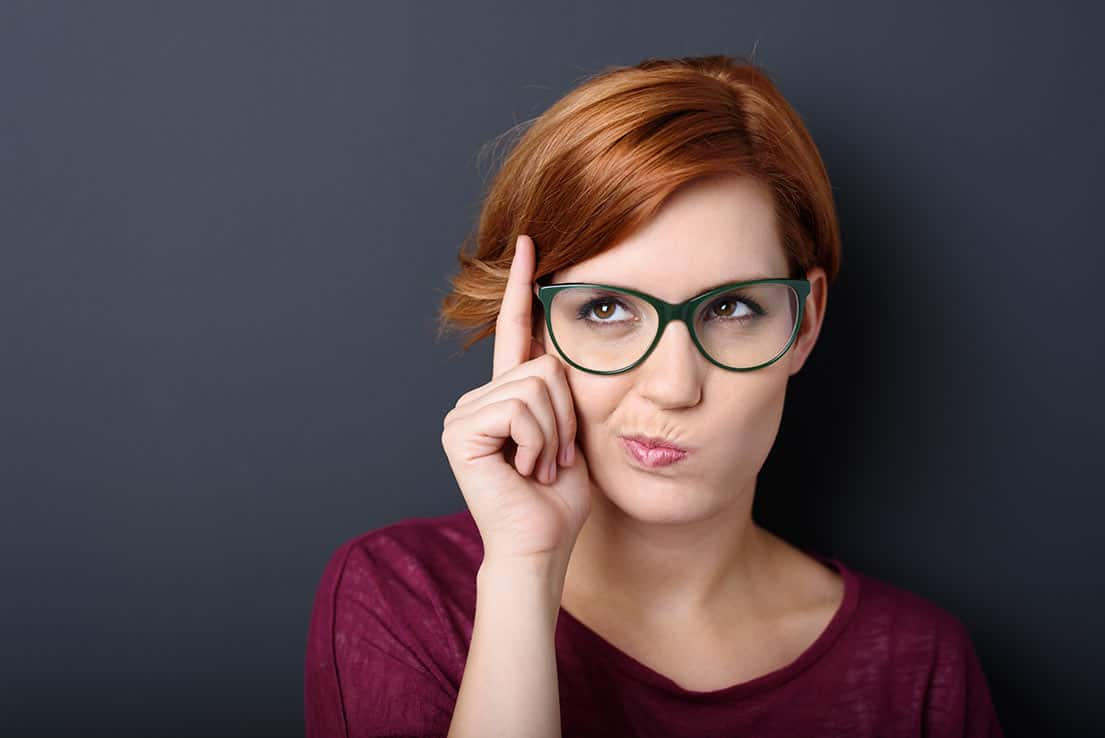 A lady wearing glasses, thinking and looking puzzled