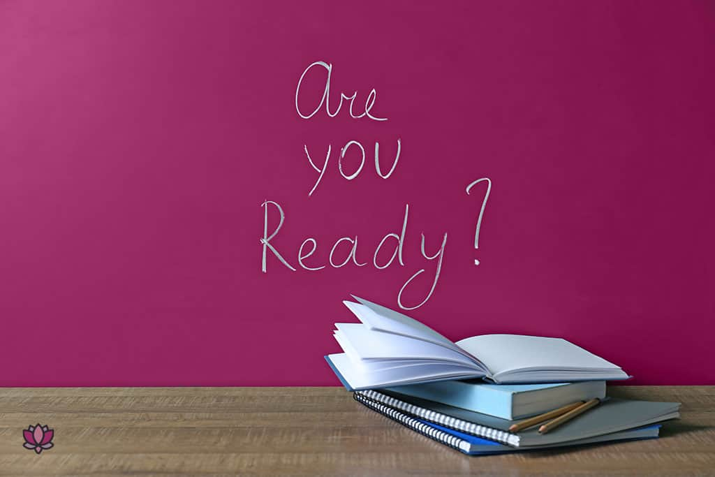 """A wall with """"are you ready?"""" written in chalk. A few books and office related items are on on a desk."""