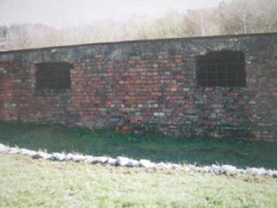 Vestiges d'un bâtiment du camp s'étirant le long de la voie de chemin de fer. Il est entouré d'un cordon de pierres blanches.