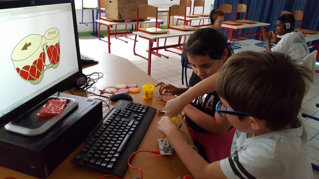 Pendant un stage PRE. Deux jeunes travaillent sur la réalisation d'une unité de contrôle de son a base de pâte a modelé