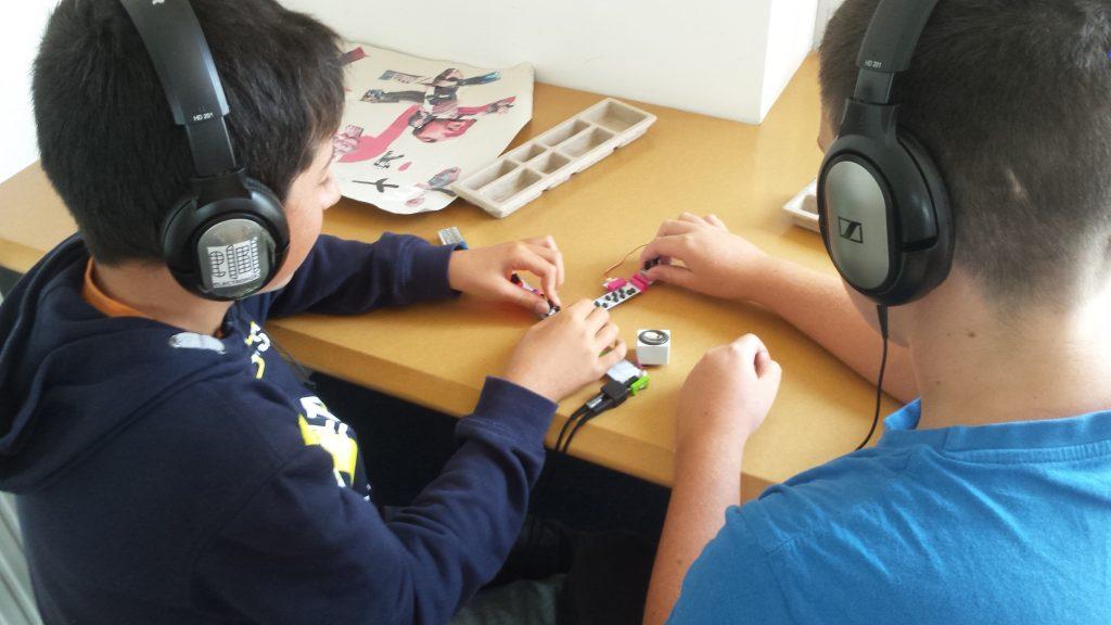 Deux jeunes élaborent un synthétiseur lors d'un atelier PRE juste avant la rentrée scolaire.