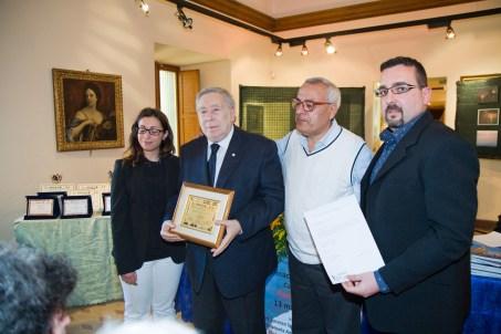Il Premio alla Carriera conferito al prof. Armando Ginesi. Consegnato da Silvia, che fa le veci di Emanuela Antonini (Presidente del Premio), il prof. Vincenzo Prediletto (Presidente di Giuria) e Lorenzo Spurio (Presidente della Ass. Euterpe)