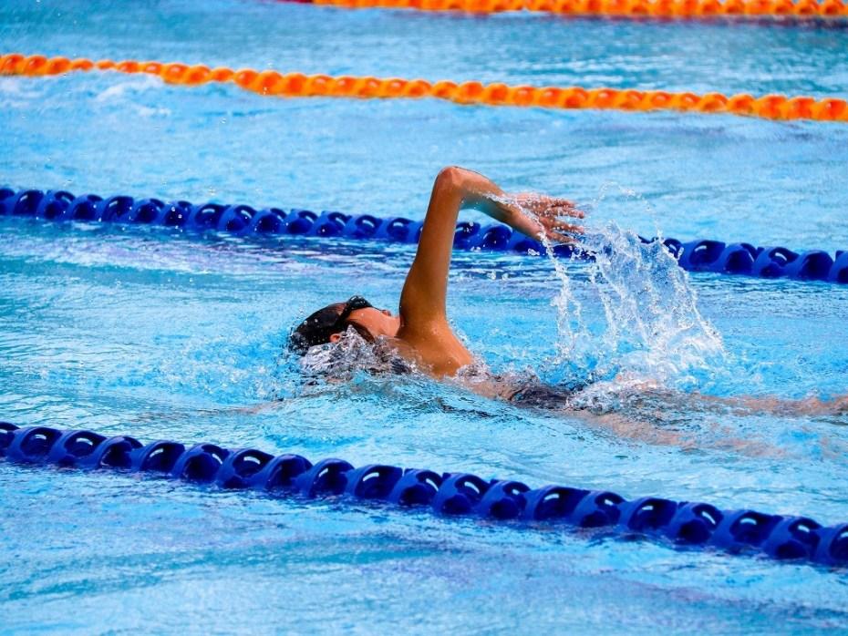 mężczyzna pływający w basenie, dlaczego warto pływać, zalety pływania