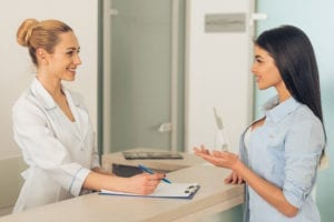 Consistently Full Dental Hygiene Schedule Requires That The Dental Front Office Gather Great Information From The Dental Patient. A Hygiene Coordinator Has A Patient At The Front Desk Filling Out Forms.