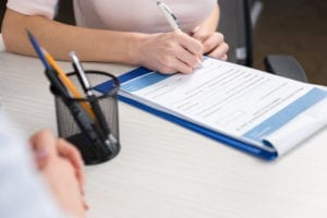 Dental Financial Agreement Being Signed By A Dental Office Patient