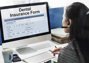 Dental Office Accounts Receivable Require Constant Attention. A Woman Sits At Her Computer Working On A Dental Insurance Claim