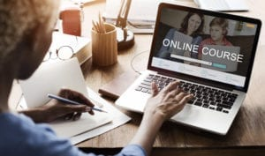 An Online Course Is Available To Improve The Dental Front Desk Management Systems. A Woman Sits At Her Laptop Taking An OnLine Course in Dental Front Desk Management Systems.