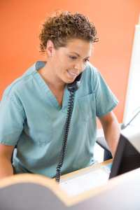 A Dental Front Office Team Member Talks On The Phone As She Schedules A New Patient