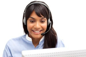 A smiling woman wearing a headset answers the telephone and is working on the computer. She is providing the best dental office customer service.