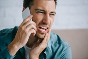 A man holds his cheek and is talking on his cell phone.  He has called the dental office for help.  Scheduling dental emergency patients is usually done over the telephone.