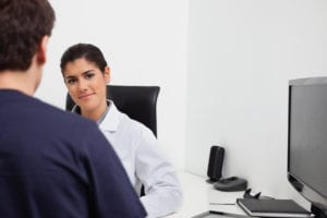 A female dentist sits at a desk talking to a male dental patient.  Scheduling dental emergency patients sometimes requires that they wait for a time when they can be worked into the schedule that day.