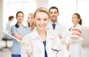 A group of dental clinicians stand together holding a toothbrush and models of teeth. Learning dental hygiene scheduling improves dental office productivity.