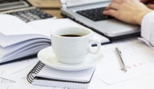 A cup of coffee sitting on a notebook symbolize the task of returning patients' calls early in the day when they have left messages over night.