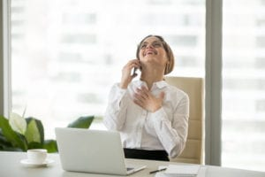 A dental front office woman laughs during a collection call. She knows that building relationships with patients is important even when making dental office collection calls.