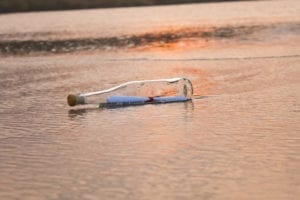 A bottle with a message inside rests in the sand. It can feel frustrating to leave messages when making dental office collection calls. It might even feel like throwing a message in a bottle into the sea.