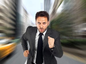A businessman runs to the dental office as he doesn't want to be one of those dental patients arriving late.