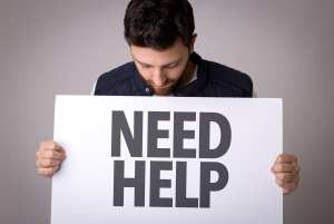 A businessman holds a sign to show that he needs help. The dental front office team must look for signs of difficult dental patient situations.