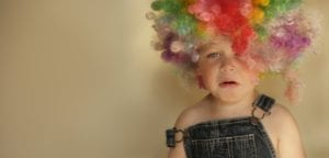 """A young child cries and wears a clown wig. He's having a bad day and represents a bad day. Difficult dental patient situations often result from a """"bad day""""."""