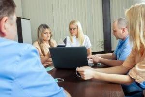 Dental office team members meet to discuss business