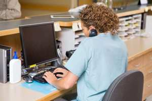 A dental front office team member sits at her desk to confirm dental appointments.