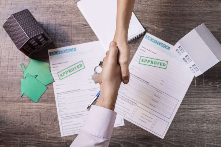 Realtor and client shaking hands in agreement (via Freepik)