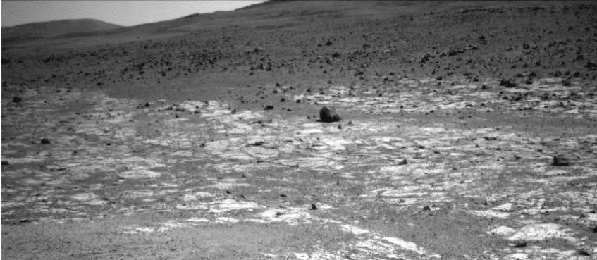 """O rover Opportunity tirou esta foto ao que vê à sua volta. Na frente, a cores claras vê-se o registo geológico conhecido como """"Burns Foundation"""". Mais atrás, mais escuro e provavelmente um registo geológico mais antigo, vê os limites de """"Solander Point"""", que se encontra na parede oeste da Cratera Endeavour. Crédito: NASA/JPL-Caltech"""