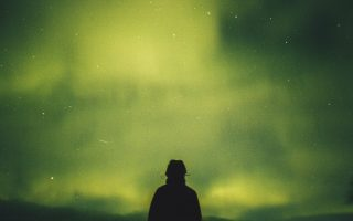 person standing under green aurora borealis