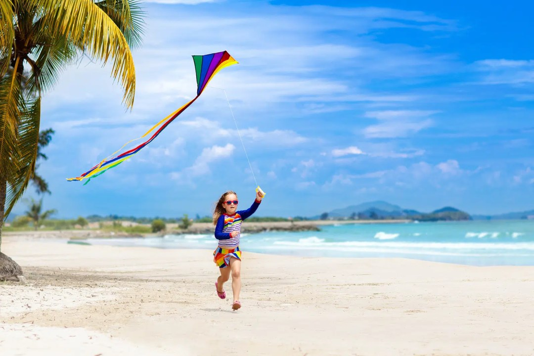 Child running with colorful kite on tropical beach.