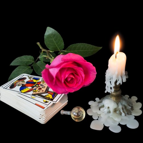 On a dark background in the light of the candles the tools of the magician: Tarot cards, a bottle of magic liquid and a symbol of love - scarlet rose.