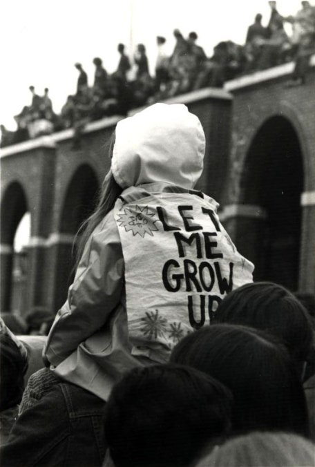 """Young child sitting on the shoulders of an adult at an Earth Day protest. Child has a sign on her back with the text """"Let me grow up"""""""