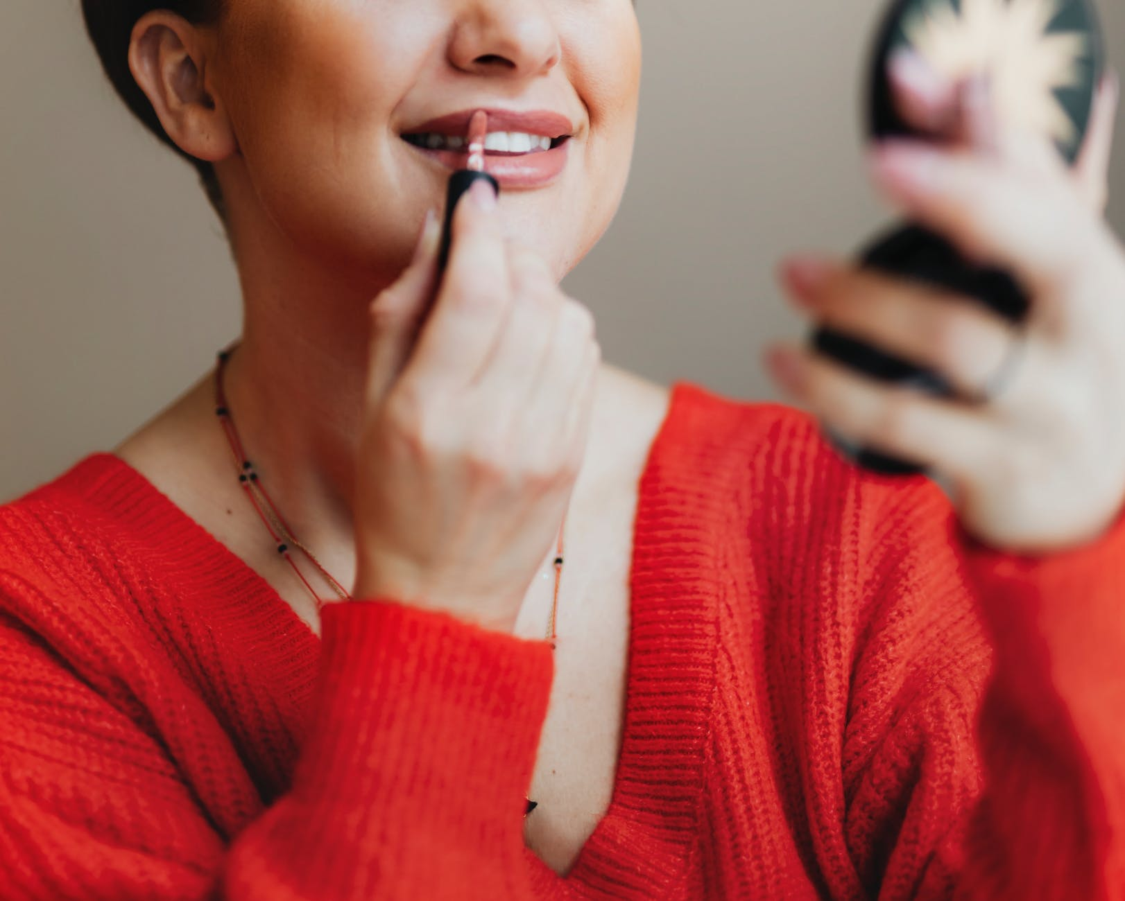woman putting lipstick while using press powder mirror