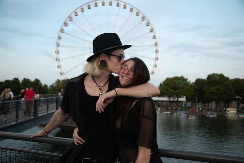 photo of couple standing near metal railings