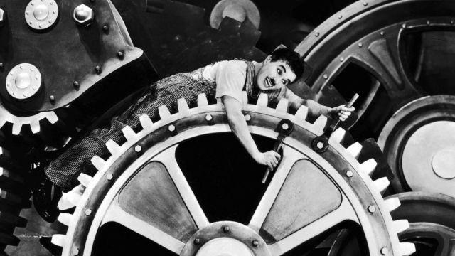 تشارلي شابلن من فيلم الأزمنة الحديثة (1936) الذي جسد فيه عبودية الإنسان للعمل واستغلاله