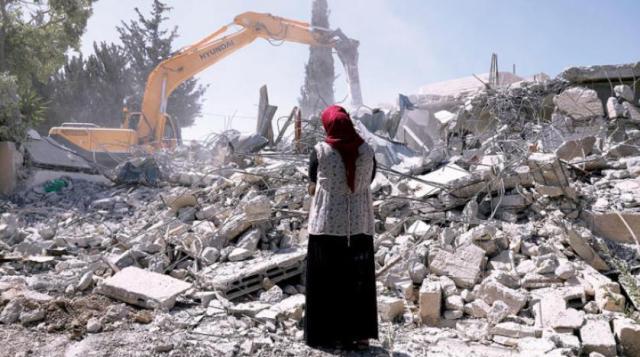 سيدة تقف أمام منزلها بعد أن تم قدمها من قِبل قوات الاحتلال