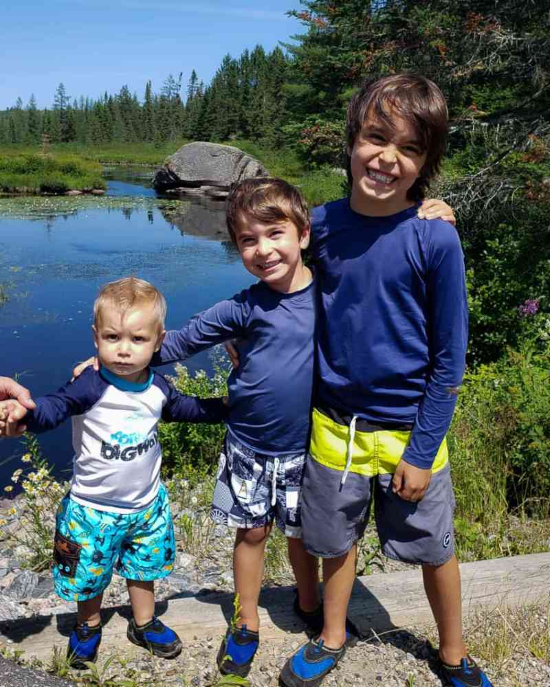 boys standing in front of a rock and lake in algonquin park