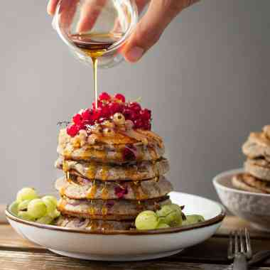 stack of gluten free pancakes topped with currants and maple syrup being poured over