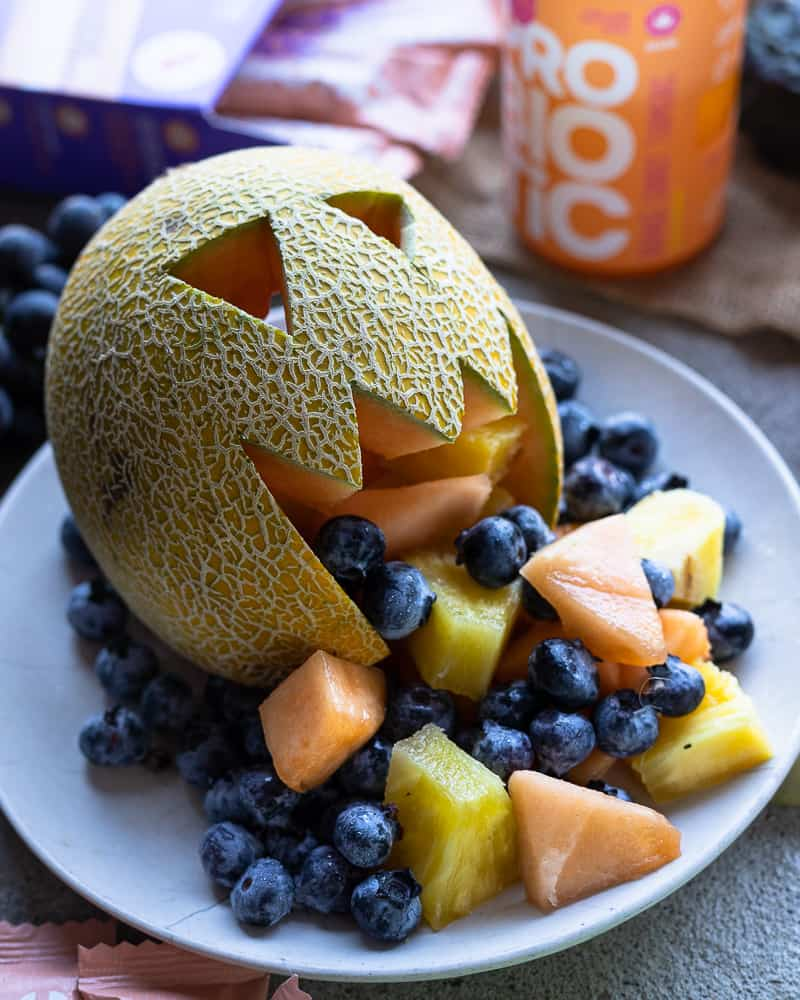 Cantaloupe cut into a face with fruit inside