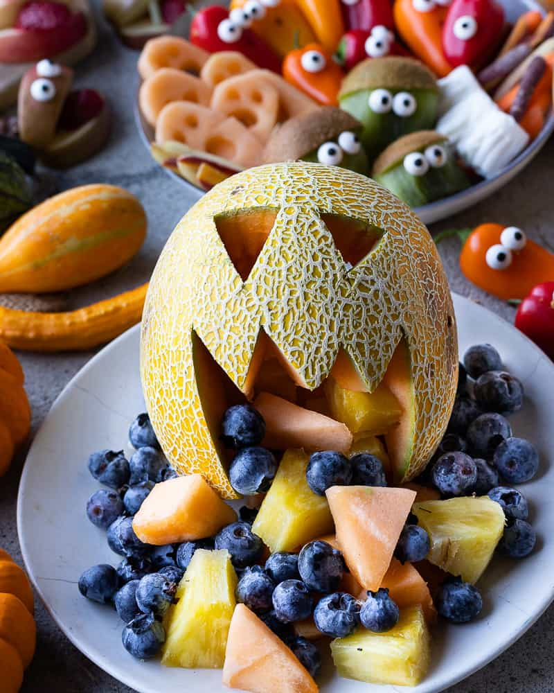 Melon cut into a jack'o'latern with fresh fruit coming out the mouth