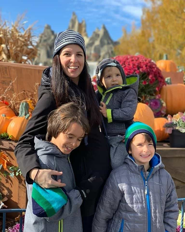 Mom and 3 kids standing in front of a pumpkin patch
