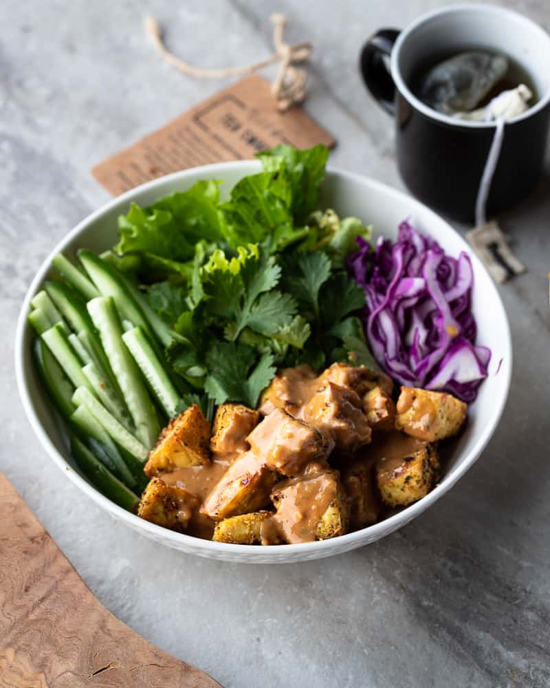 bowl of fresh veggies and tofu in a peanut sauce served with tea