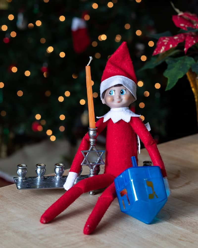 Elf on a shelf on a menorah holding a dreidel