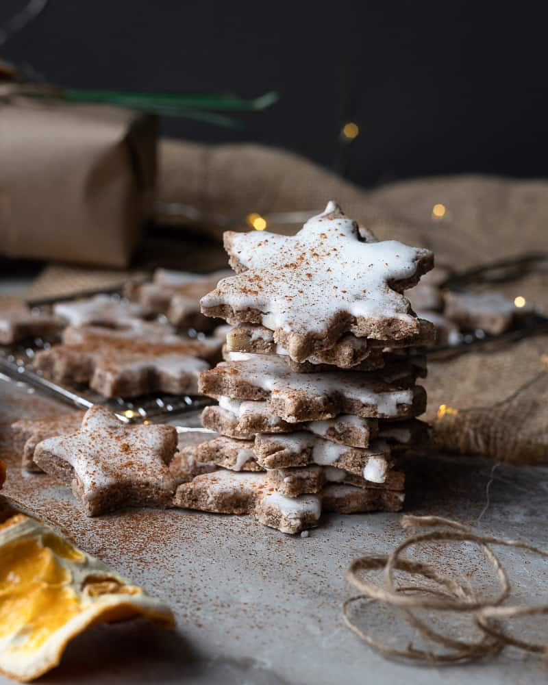 Stack of german cinnamon star cookies with twinkly lights in the background