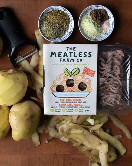 Meatless farm ground vegan meat on a cutting board with peeled potatoes and spices