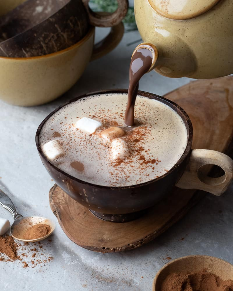 hot chocolate being poured from a pot into a cup