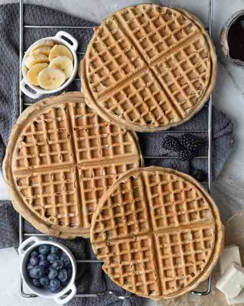 3 waffles cooling on a rack surrounded by banana, blueberries and maple syrup