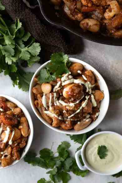 bowls on easy vegetable Morrocan stew on the dinner table with small bowl of cilantro creme