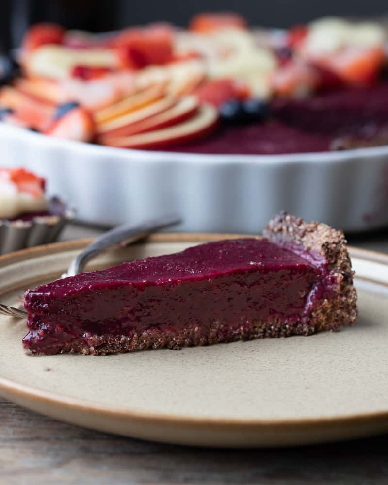 Straight view of a slice of no bake berry pie with a granol bar crust