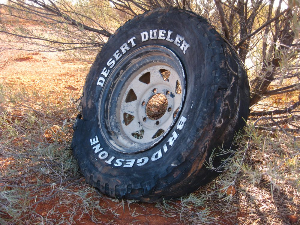 Destroyed Desert Dueler wheel on the side of a road.